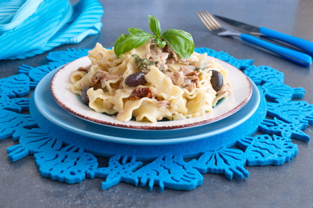 Pasta with olives, tuna, sun dried tomatoes and olive oil in a white and blue plate on a blue cloth. Stock Photo