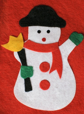 Woolen snowman isolated on a red background photo