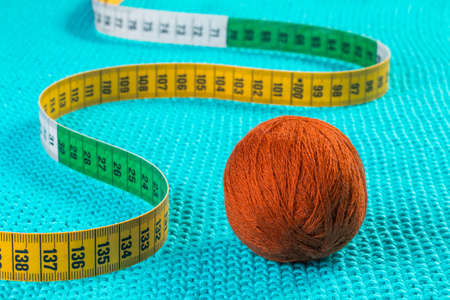 Orange ball of thread and a colored ruler on a knitted blue background