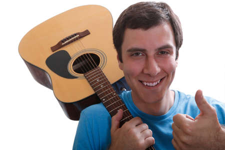 Smiling young man holding his guitar on his shoulder and pointing up with his left hand thumb.