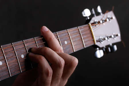 Male hand holding a barre on the acoustic guitar, close-up on a black background