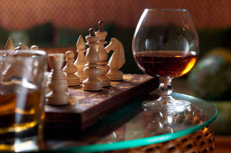 Chess-board and chess pieces, a goblet of wine and a glass of whiskey on a transparent table