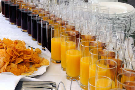 Rows of glasses of juice and a pile of chips