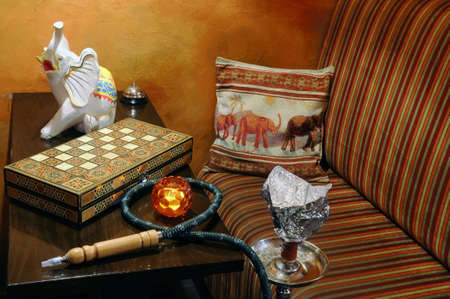 Restaurant interior still life, with a hookah, a chess-board, an elephant figurine