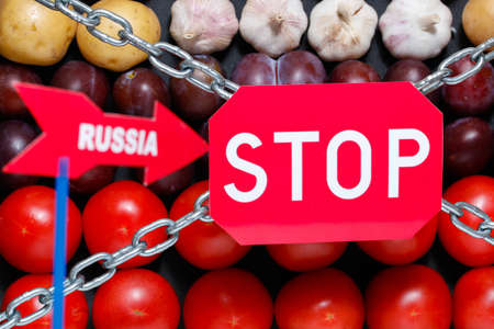 Stop and Russia signs on a vegetables background, in context of sanctions and extermination of food in Russia
