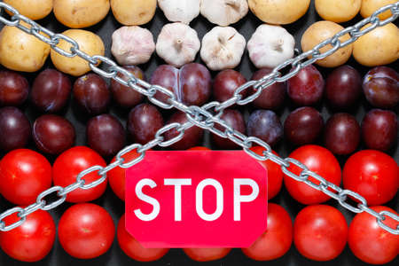 Chain and a stop sign on a vegetables background, in context of sanctions and extermination of food in Russia