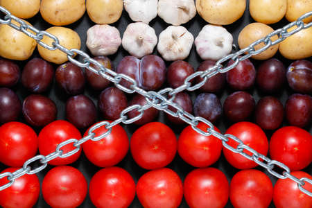 Chain on a vegetables background, in context of sanctions and extermination of food in Russia Stock fotó