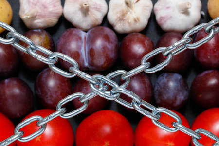 extermination: Chain on a vegetables background, in context of sanctions and extermination of food in Russia Stock Photo