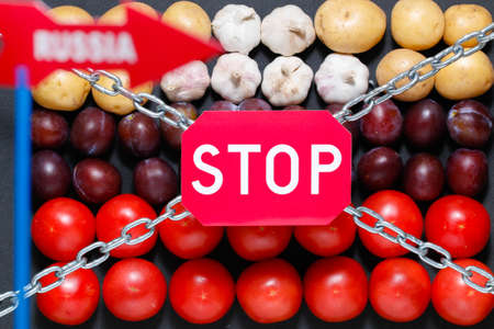 Chain, a stop and a Russia sign on a vegetables background, in context of sanctions and extermination of food in Russia