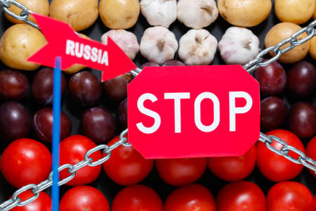 extermination: Stop and Russia signs on a vegetables background, in context of sanctions and extermination of food in Russia