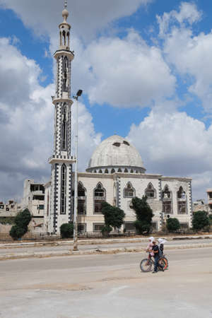 Homs, Syria - September 23: Children pass by a damaged mosque on September 23, 2013 in Homs, Syria. The mosque had been damaged in a fighting between the Syrian National Army and rebels during Syrian civil war