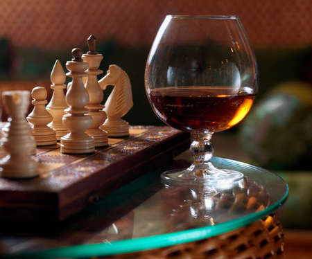 ajedrez: Tablero de ajedrez y piezas de ajedrez, una copa de vino y un vaso de whisky en una mesa transparente