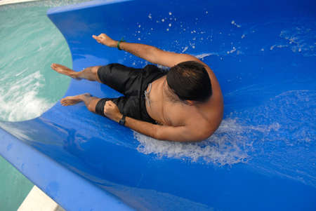 Man sliding into a swimming pool