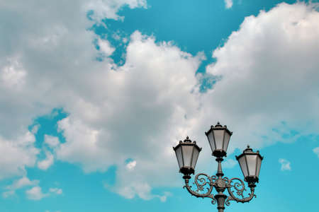 Vintage street lantern against the blue cloudy sky