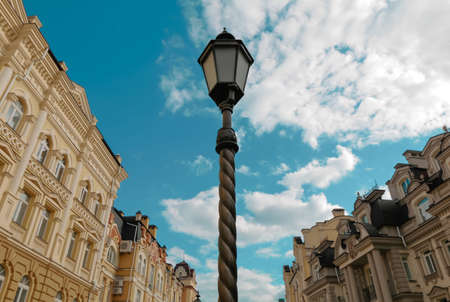 Vintage street lantern against blue cloudy sky