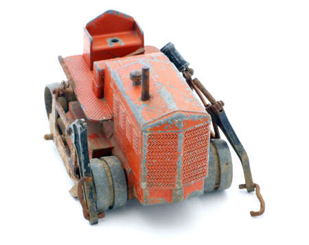Rusty old red toy tractor with peeling paint.  photo