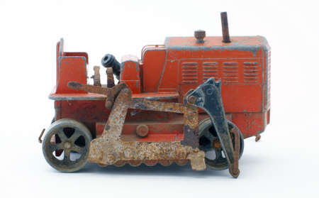Old red toy tractor with peeling paint.  photo