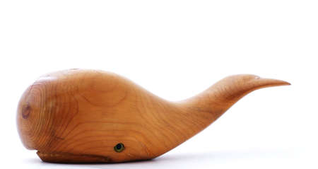 Hand carved wood whale with flukes elevated. Фото со стока
