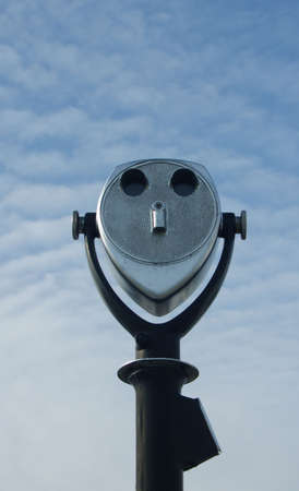 Powerful coin operated binoculars with blue sky and clouds. photo