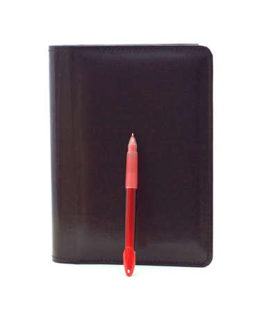 A daily leather organizer with a bright red pen.