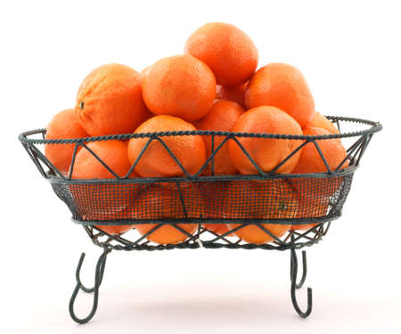 wire mesh: Fresh juicy tangerines in a wire and mesh metal basket.