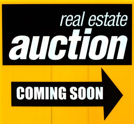 auctioning: A real estate action sign advertising a coming sale.