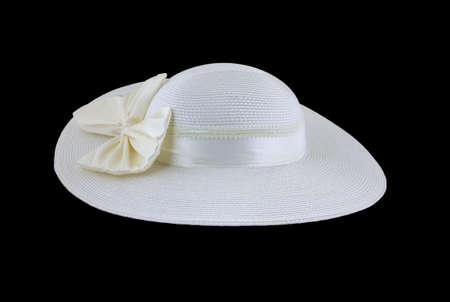 white trim: Side view of a womans white wide brimmed fancy dress hat against a black background.  Stock Photo