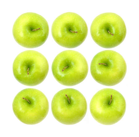 Three rows of the tops of Granny Smith apples against a white background.  photo