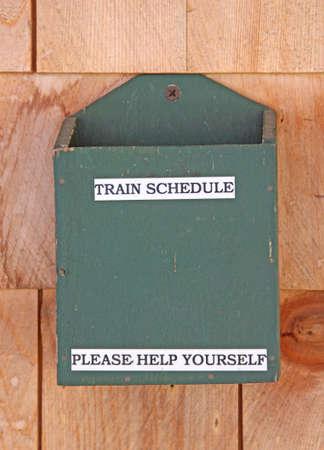 An empty train schedule holder screwed to cedar shingle siding. Stock Photo - 5299178