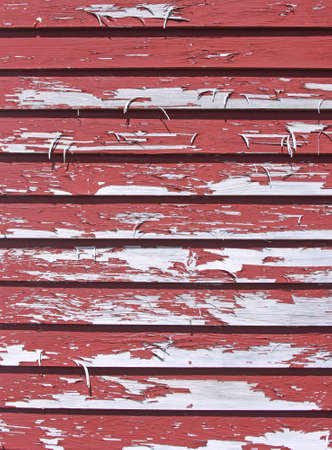 Weather worn red paint peeling from clapboard siding.