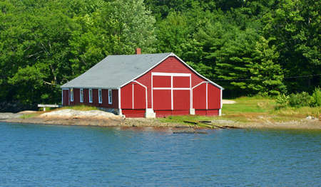 white trim: A red storage building near the ocean with white trim.