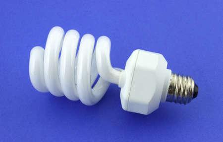 A compact fluorescent light bulb against a blue background.  photo