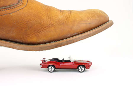 top down car: A small toy convertible car about to be crushed by a mans boot.  Stock Photo