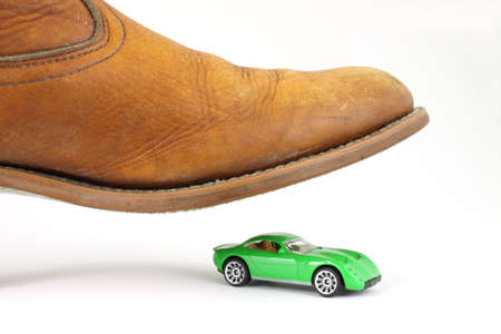 imminent: A green toy sports car about to be stepped on by a large mens boot. Stock Photo