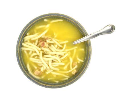 Een dienstverlening van mie soep kip in een kleurrijke schotel met lepel tegen een witte achtergrond.