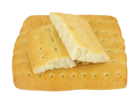 A full piece of focaccia bread with two broken pieces on top against a white background.