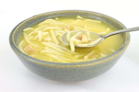 meat soup: A serving of chicken noodle soup in an old bowl with a spoon.