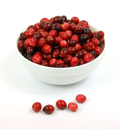 Several ripe and ripening cranberries in a white bowl with berries in front.