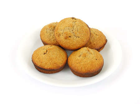 Freshly home baked bran muffins with dates on a plate against a white background.  photo