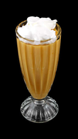 A large glass dessert dish filled with sugar free butterscotch pudding and no calorie whipped cream against a black background.