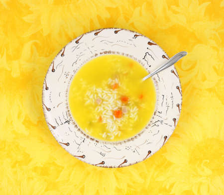 A serving of chicken with rice and vegetables soup in a colorful dish with spoon on a bright yellow cloth.  photo