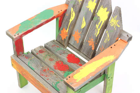 wood lawn: A hand made wood lawn chair for children with colorful paint showing hearts and worn blotches.