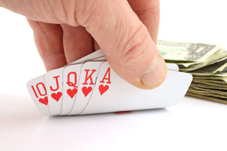 Mans hand holding a royal flush with cash in the background photo