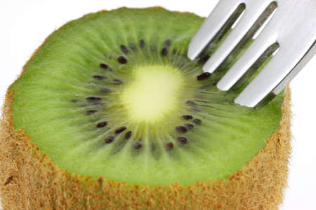 A close view of fresh cut Kiwi fruit with a fork. photo