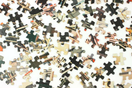 An assortment of pieces of an old jigsaw puzzle on a white surface. photo