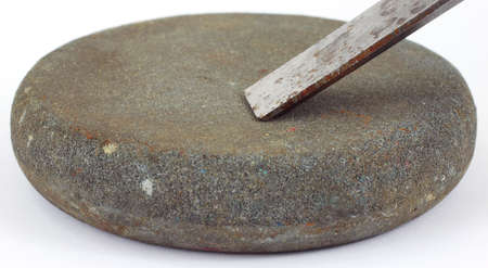 hardened: A small round whetstone with a cold chisel being sharpened.