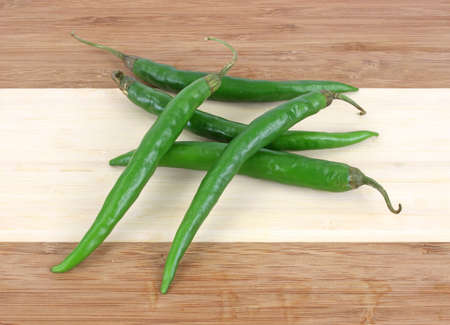 Several long green hot peppers on a wood cutting board. Stok Fotoğraf