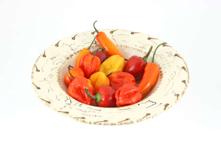 A bowl full of colorful chili peppers on a white background.