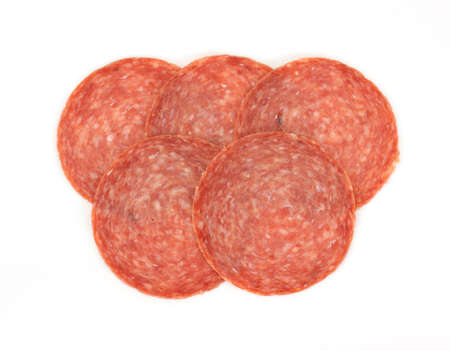 A group of five slices of hard salami on a white background.