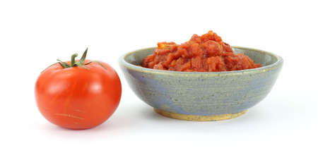 old items: A single red and juicy ripe tomato next to a bowl of freshly crushed tomatoes on a white background.